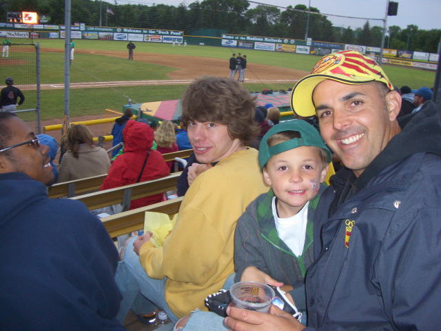 Miles Hungsberg-Perzewski (in yellow) and father and son, Brook and Dylan Anthony, enjoy the game.